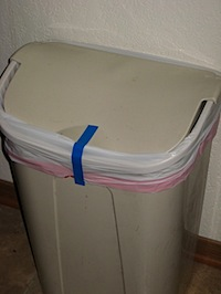 Babyproof a trash can with tape